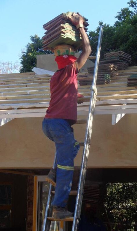 A person carrying pieces of roofing on his head as he climbs a ladder